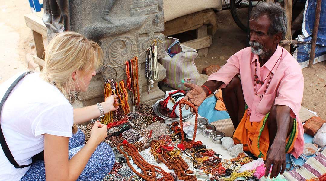 Pige køber smykker ved bod på markedet