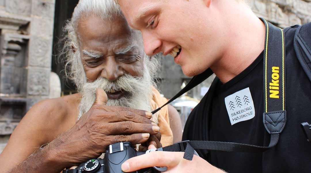 Ung dansker og ældre inder kigger på foto på kamera