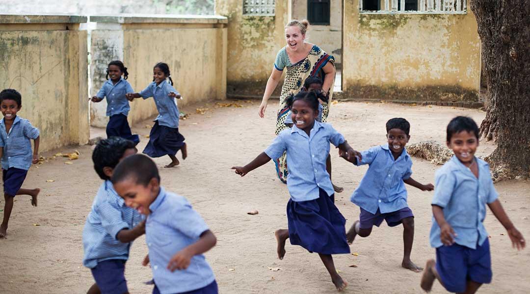 Pige leger med børn i skolegård